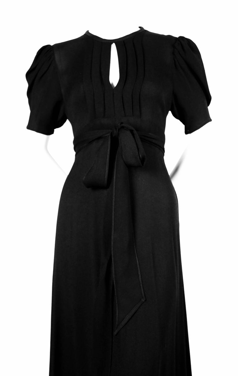 Jet-black, moss crepe wrap dress with pintucks, keyhole neckline and open back designed by Ossie Clark for Radley. Best fits a size 4-6. Wrap closure at waist and tie at back of neck.  Made in England. Excellent condition.