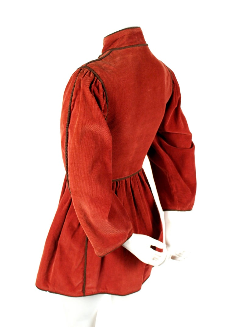 Very rare dark cinnabar red corduroy coat trimmed in brown cording with wood buttons designed by Yves Saint Laurent dating to the 1976 Russian collection. Coat is labeled a French size 34 and fits a US size 0/2. Approximate measurements: shoulder
