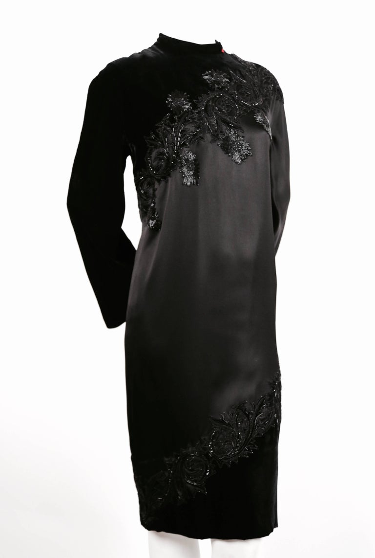 Very rare jet black silk satin and velvet haute couture dress with unique spiral design and elaborate beading designed by Pierre Balmain dating to the 1960's. Dress has a red bow at neckline which indicates that it was made for a recipient of the