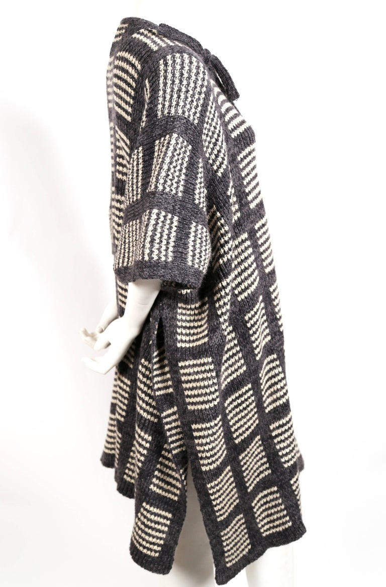 Heathered grey and off-white knit poncho cape coat designed by Issey Miyake dating to the 1970's. Ties at neck. Fabric content: 50% wool 30% silk, 10% acrylic and 10% nylon. Made in Japan. Excellent condition.