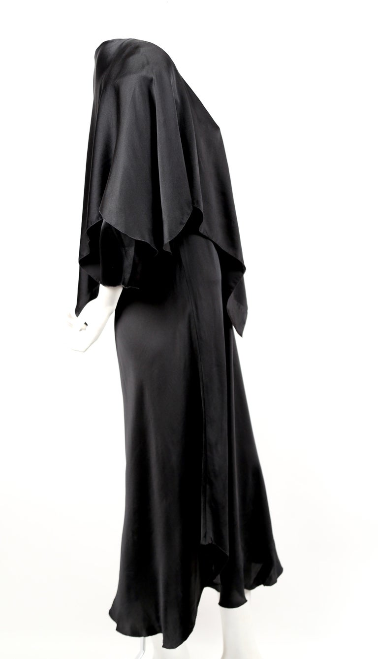 Black, bias-cut silk dress with uneven hemline and cape designed by Sonia Rykiel dating to the 1970's. No size is indicated however this is best suited for a US 2-4. Approximate measurements: 32