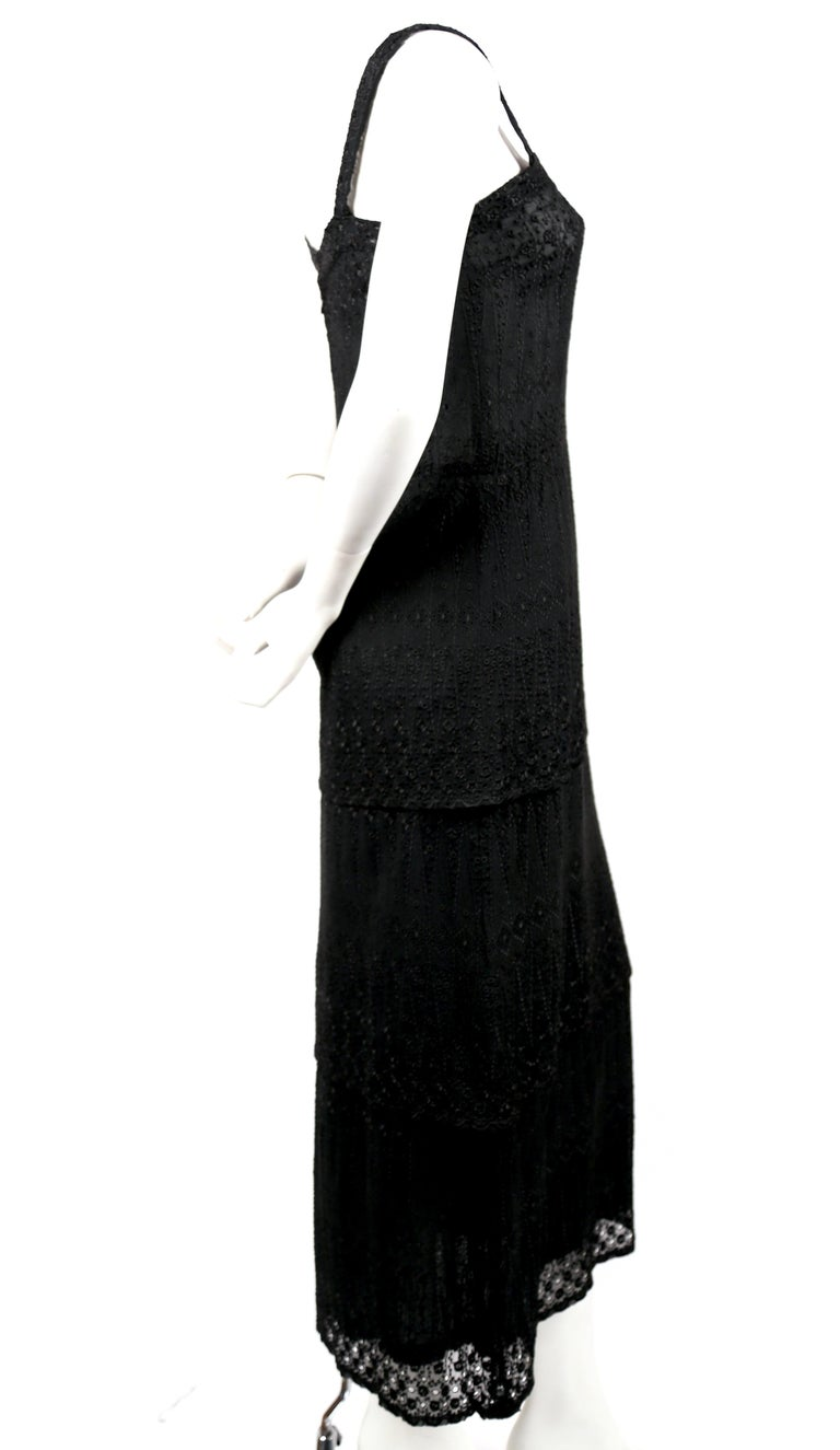 Black eyelet lace dress with tiered hemline designed by Ted Lapidus dating to the 1970's. Best fits a US 2-4. Approximate measurements: bust 32