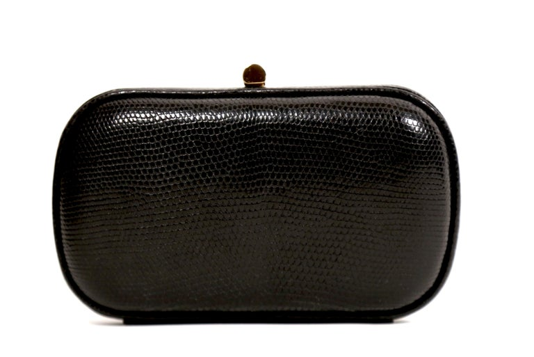 Black karung lizard clutch with gold-toned hardware, black satin lining and push-lock closure designed by Bottega Veneta dating to the 1980's. Approximate measurements: 6.25