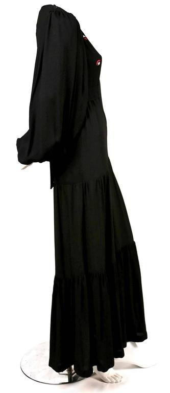 """Very rare tiered black moss crepe dress with large bishop sleeves and embroidered stars and moons from Ossie Clark for Quorum. Labled a UK size 8. Approximate measurements: shoulder 13"""", bust 32"""", waist 26"""", hips 36"""", arm length"""