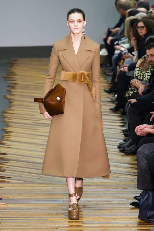 Camel wool gaberdine coat with narrow arms and flared hemline designed by Phoebe Philo for Celine exactly as seen on the fall 2014 runway. French size 40 which fits a US 6-8. Made in Italy. Fully lined. Pockets at hips. New with tags. Original