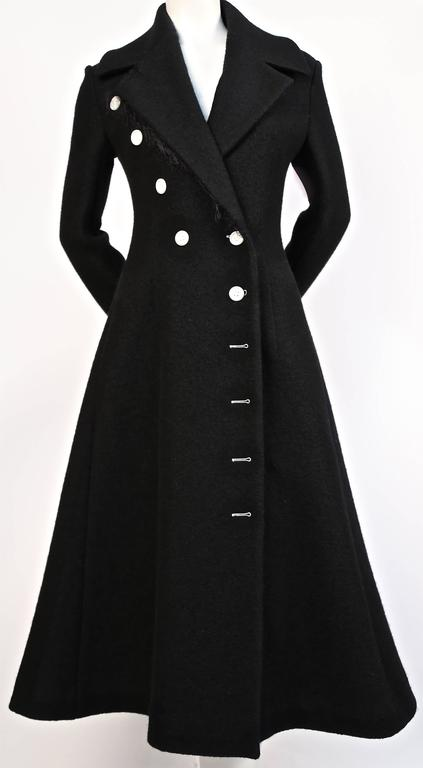 """Jet black textured wool coat with asymmetrical buttons and fringe trim at back of sleeves designed by Phoebe Philo for Celine as seen on the fall 2014 runway. French size 42 which fits a US 8. Approximate measurements: shoulders 17"""", bust 36"""", waist"""