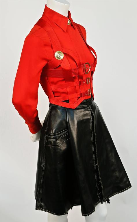 Iconic and very rare Gianni Versace Couture red silk topstitched bondage harness bodice with gold-toned Medusa embossed hardware, matching silk blouse and black leather skirt designed by Gianni Versace exactly as seen in the Fall 1992 Bondage runway
