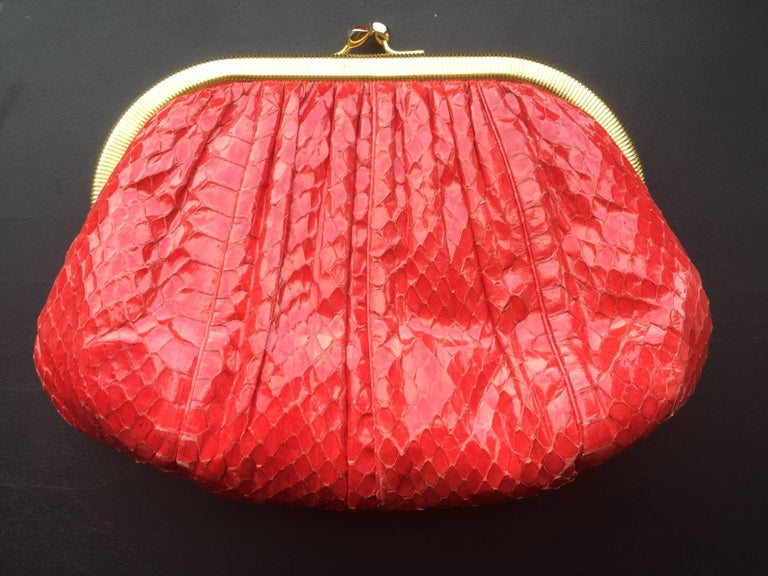 This Judith Leiber clutch is from the early 1980s.  This snakeskin clutch features gold hardware, snap closure, and an optional gold chain shoulder strap. The inside has a silk lining and small zipper pocket. The piece can be used as a shoulder bag