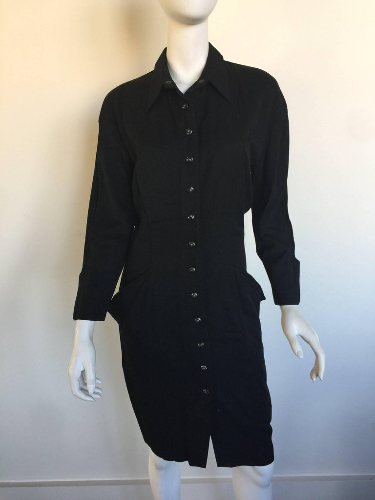 """This black tailored Thierry Mugler dress is from the early 90s. This tailored shirt dress is wool gabardine and has front snap closures, from the neck to 8"""" above the hem.  It has decorative futuristic pockets, signature of Mugler.  The dress"""