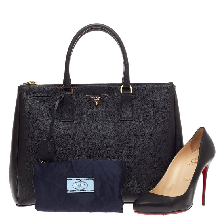 This authentic Prada Double Zip Lux Tote Saffiano Leather Medium is elegant in its simplicity and structure. Crafted from sturdy cross-grained nero black saffiano leather, this tote features, dual-rolled handles, raised Prada logo, leather clochette