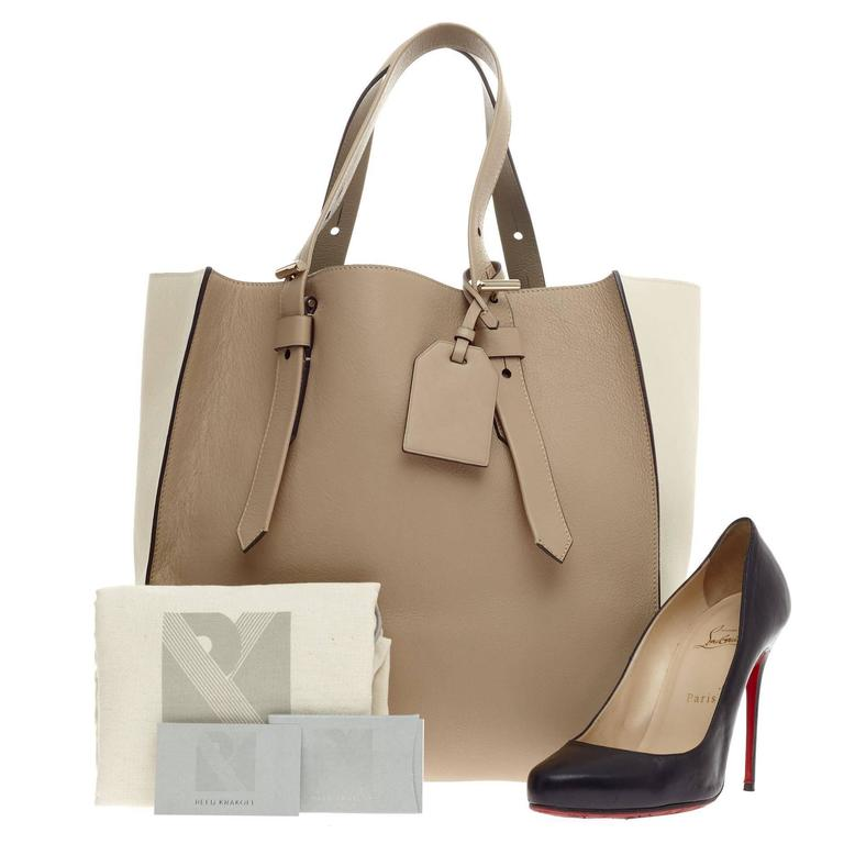 This authentic Reed Krakoff Krush Tote Leather complements both dressy and casual looks perfect for the modern woman. Crafted from bicolor beige and nude leather, this minimalist yet modern tote features dual flat tall handles, signature T bar