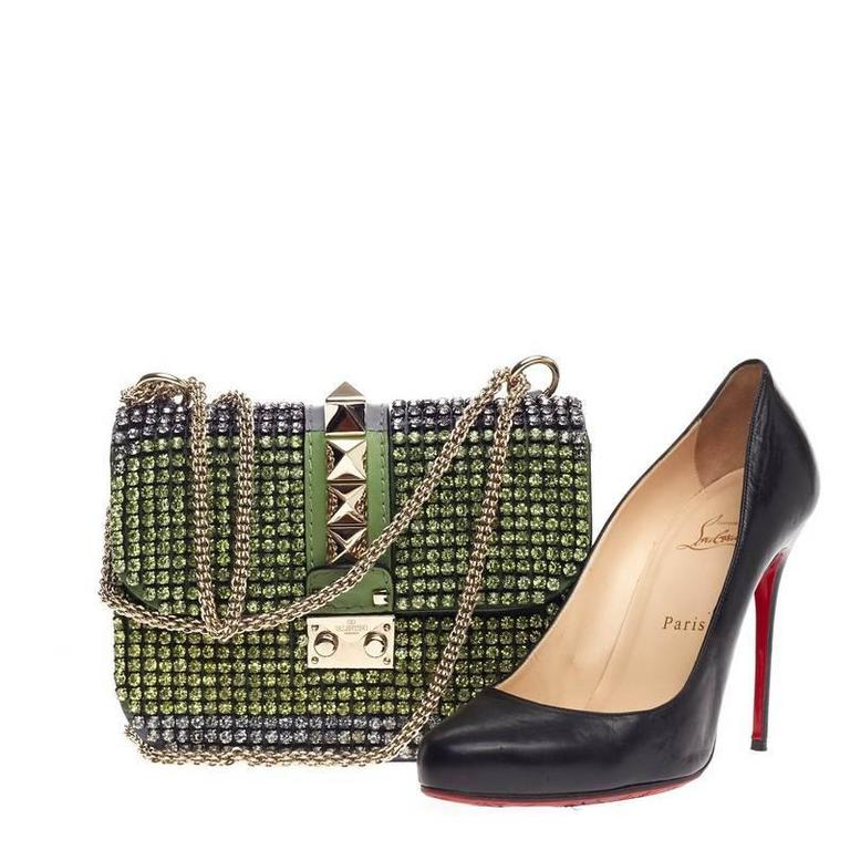 This authentic Valentino Glam Lock Shoulder Bag Crystal Embellished Leather Small is a fun, flirty and feminine accessory perfect for day to night excursions. Crafted in green and silver rhinestones with dark gray leather paneling, this eye-catching