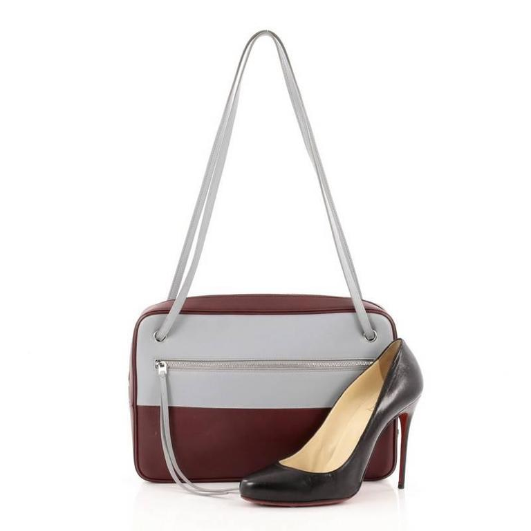 This authentic Celine Bicolor Side Lock Bag Leather Medium presented in the brand's 2013 Collection perfect for the modern fashionista. Crafted from bicolor blue gray and burgundy leather, this chic bag featured dual fat shoulder straps, exterior