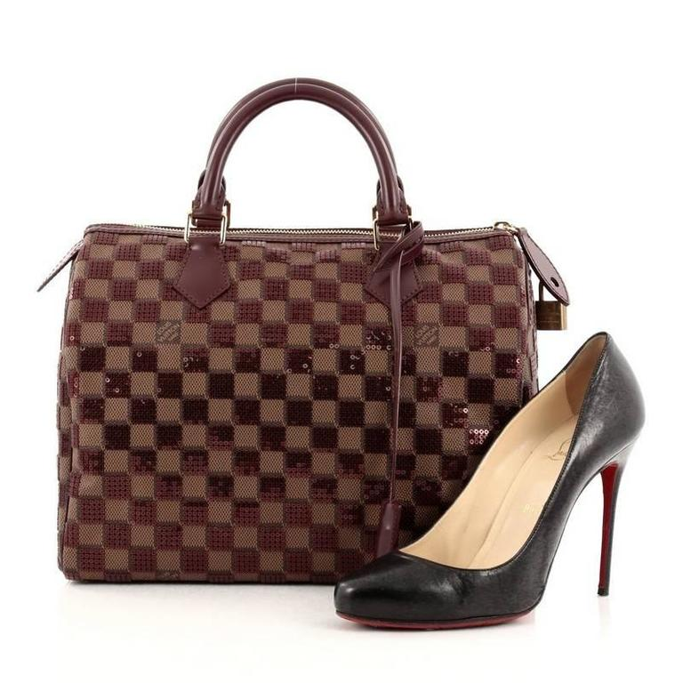 This authentic Louis Vuitton Speedy Handbag Damier Paillettes 30 inspired by the geometric spirit of the brand's Spring/Summer 2013 Collection is a sophisticated and glamorous must have made for any Louis Vuitton lover. Constructed in damier ebene