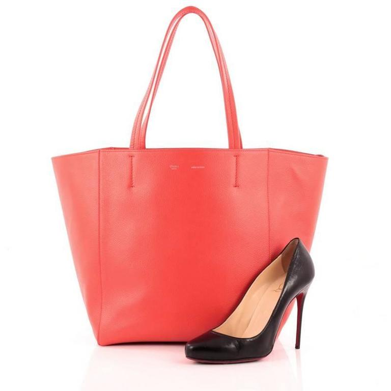 This authentic Celine Phantom Cabas Tote Leather Small is the perfect everyday shopper bag holding all essentials. Crafted in striking red leather, this tote features dual slim leather handles, stamped silver Celine logo and extended side ties and