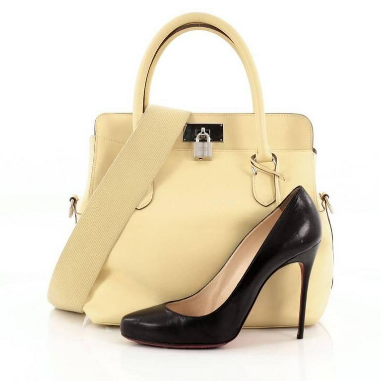 This authentic Hermes Toolbox Handbag Swift 26 presented first in the the brand's Fall/Winter 2010 Collection is a classic, luxurious piece essential for any Hermes lover. Crafted from soufre yellow swift leather, this demure yet elegant tote