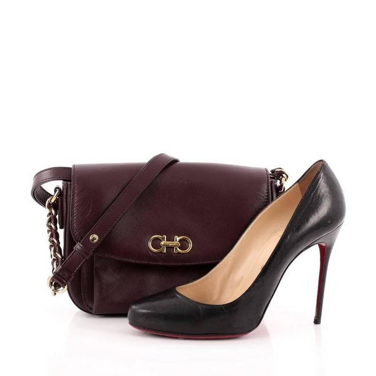 This authentic Salvatore Ferragamo Sandrine Shoulder Bag Leather is perfect for on-the-go fashionistas. Crafted in burgundy textured leather, this shoulder bag features a long leather strap with chains, Gancini gold logo at its flap and gold-tone