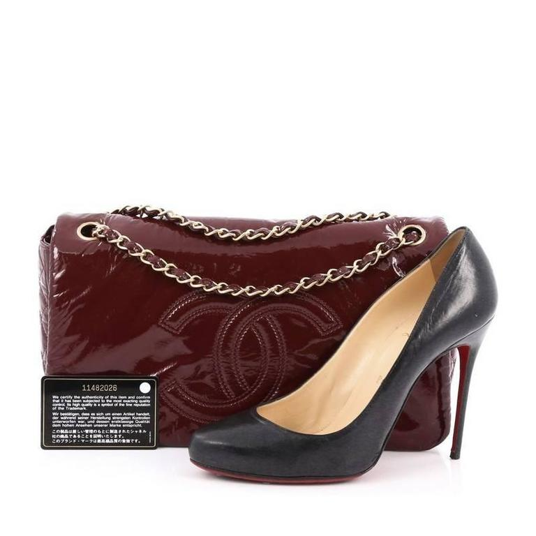 001648732680 This authentic Chanel Rock and Chain Flap Bag Patent Vinyl Medium boasts a  stature perfect for