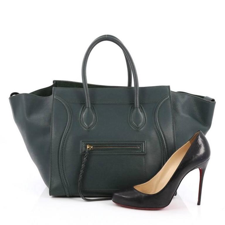 This authentic Celine Phantom Handbag Smooth Leather Medium is one of the most sought-after bags beloved by fashionistas. Crafted from dark green leather, this minimalist tote features dual-rolled handles, an exterior zip pocket with braided zipper