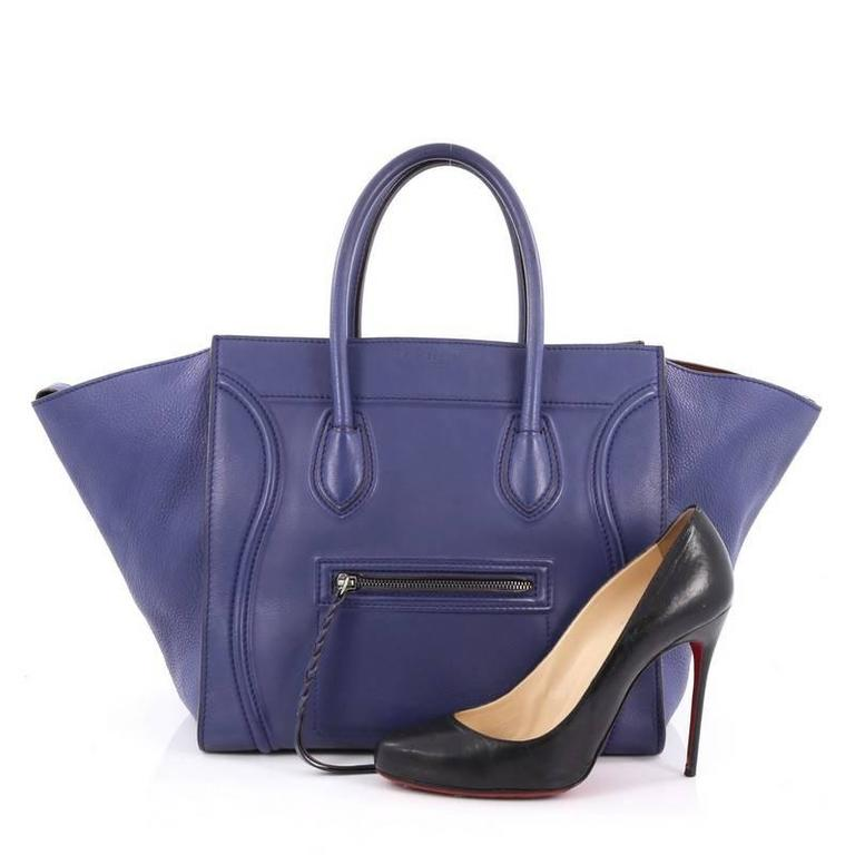 This authentic Celine Phantom Handbag Smooth Leather Medium is one of the most sought-after bags beloved by fashionistas. Crafted from sleek smooth blue leather, this minimalist tote features dual-rolled handles, an exterior zip pocket with braided