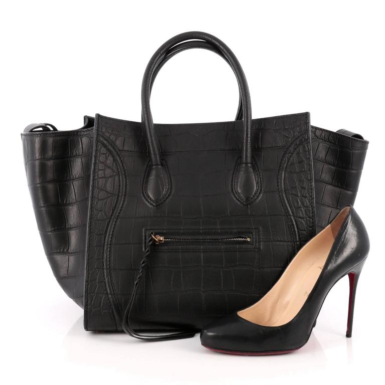 This authentic Celine Phantom Handbag Crocodile Embossed Leather Medium is one of the most sought-after bags beloved by fashionistas. Crafted from black crocodile embossed leather, this minimalist tote features dual-rolled handles, an exterior front