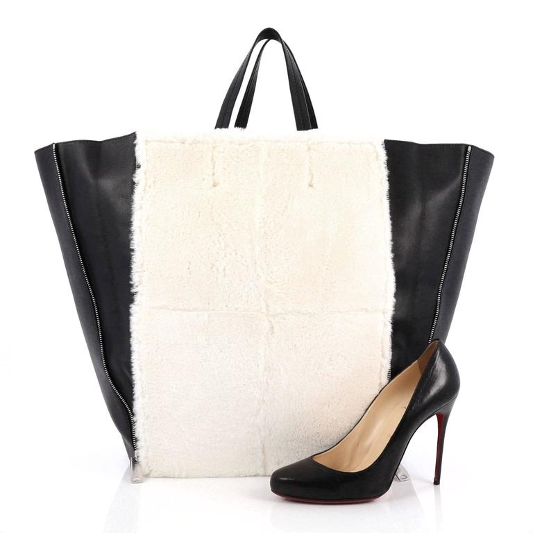This authentic Celine Vertical Gusset Cabas Tote Shearling and Leather Large combines the brand's minimalist style with beautiful craftsmanship and attention to detail. Constructed in white shearling with black leather detailing, this lightweight