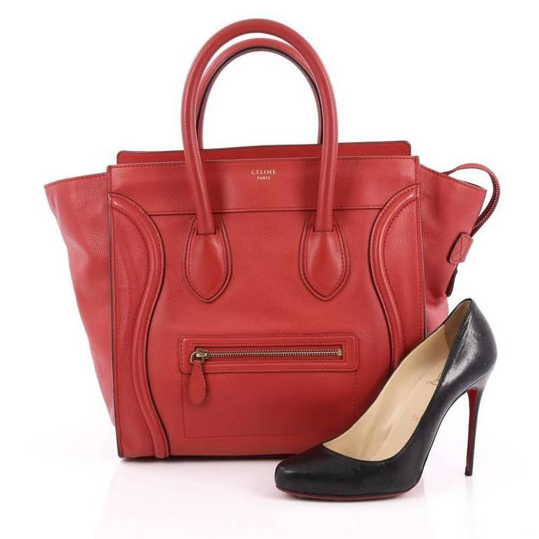 This authentic Celine Luggage Handbag Grainy Leather Mini epitomizes Phoebe Philo's minimalist yet chic style. Constructed in red grainy leather, this beloved fashionista's bag features dual-rolled leather handles, a frontal zip pocket, Celine's