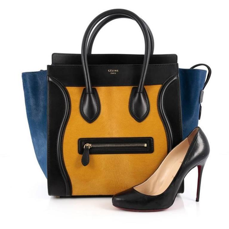 This authentic Celine Tricolor Luggage Handbag Pony Hair and Leather Mini is one of the most sought-after bags beloved by fashionistas. Crafted from genuine tricolor yellow and blue pony hair with black leather, this minimalist tote features
