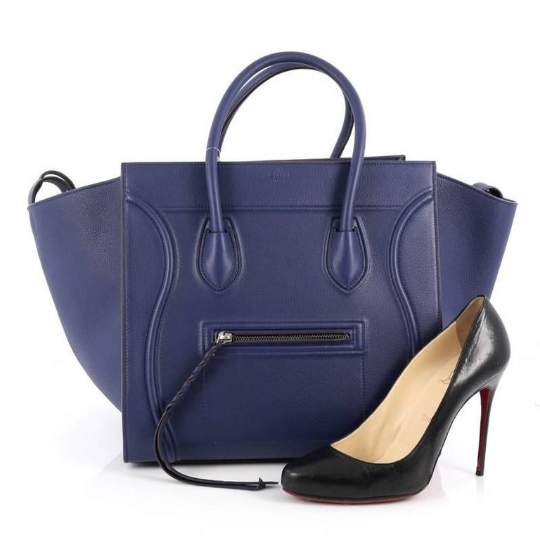 This authentic Celine Phantom Handbag Grainy Leather Medium is one of the most sought-after bags beloved by fashionistas. Crafted from blue grainy leather, this minimalist tote features dual-rolled handles, an exterior front pocket, protective base