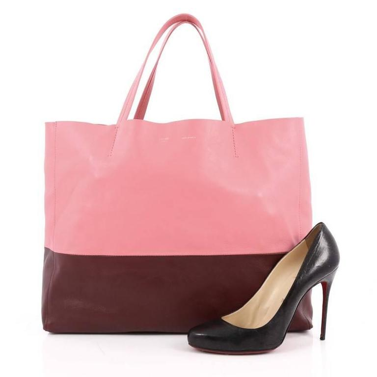 This authentic Celine Horizontal Bi-Cabas Tote Leather Large is the perfect oversized easy companion to fit all your essentials and more. Crafted in bicolor maroon and pink leather in a minimalist design, this no-fuss tote features dual flat leather