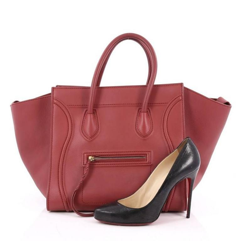 This authentic Celine Phantom Handbag Grainy Leather Medium is one of the most sought-after bags beloved by fashionistas. Crafted from red grainy leather, this minimalist tote features dual-rolled handles, an exterior front pocket, protective base