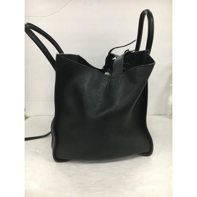 This authentic Celine Phantom Handbag Grainy Leather Medium is one of the most sought-after bags beloved by fashionistas. Crafted from black grainy leather, this minimalist tote features dual-rolled handles, an exterior front pocket, protective base