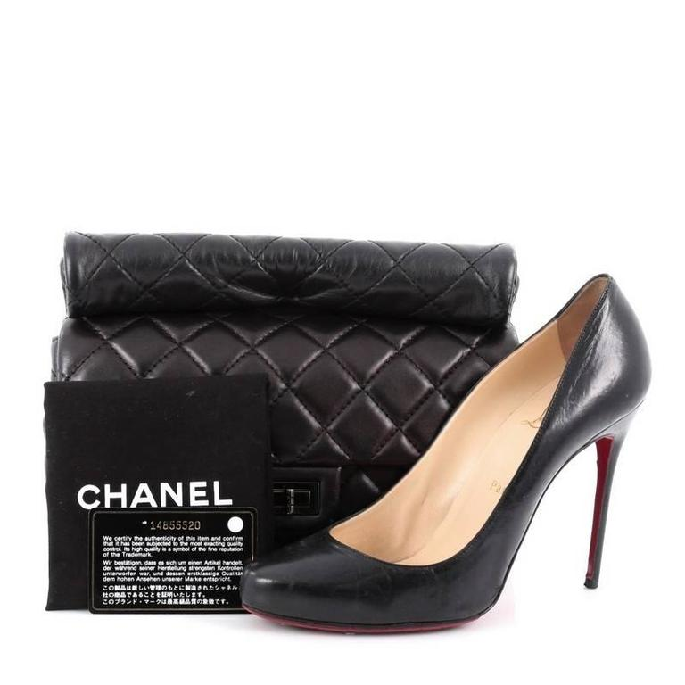 This authentic Chanel Reissue Roll Clutch Quilted Lambskin Medium is ideal for nights out. Crafted in black diamond quilted lambskin leather, this clutch features rolled top handle, frontal flap, exterior back pocket and gunmetal-tone hardware