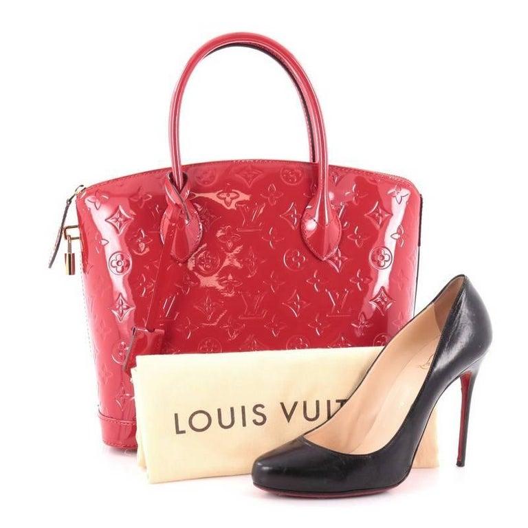 67cb8ec498ef This authentic Louis Vuitton Lockit Handbag Monogram Vernis PM mixes the  brand s penchant for timeless designs