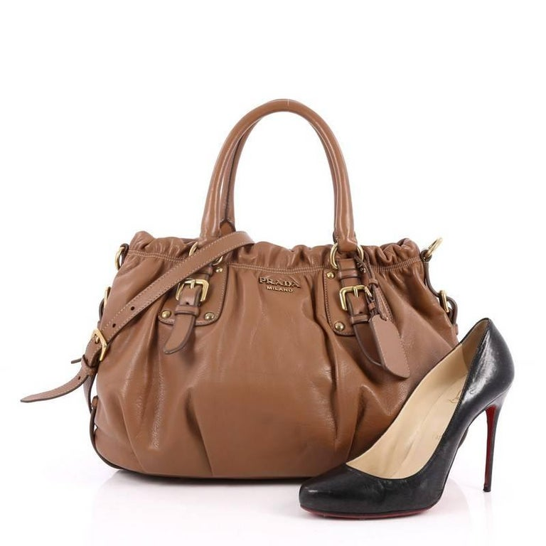 This authentic Prada Convertible Belted Satchel Cervo Leather Medium is a beautifully and intricately crafted bag perfect for everyday use. Constructed in brown cervo antik leather, this bag features dual-rolled handles, belted sides, trademark