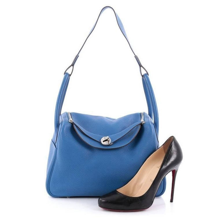 This authentic Hermes Lindy Handbag Clemence 30 is the perfect understated accessory for the modern woman. Crafted from blue electric clemence leather, this no-fuss shoulder bag features dual rolled handles, two sides slip pockets, protective base