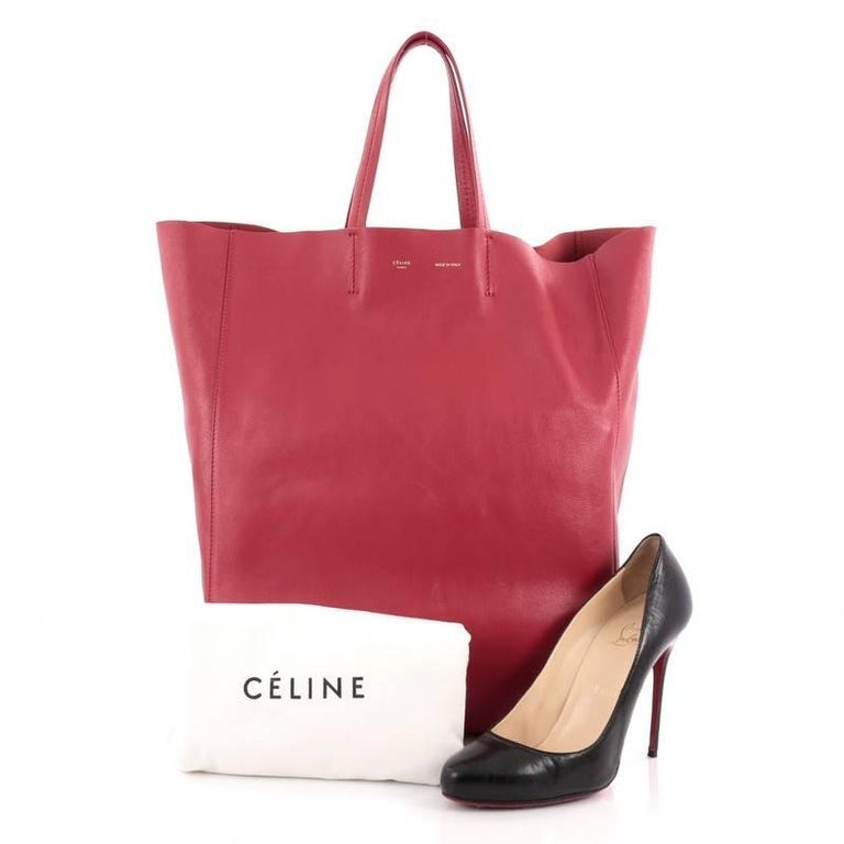This authentic Celine Vertical Cabas Tote Leather Large is a perfect everyday accessory for the woman on-the-go. Crafted in red leather, this minimalist bag features slim handles and gold stamped brand name. It wide top opening showcases a roomy red