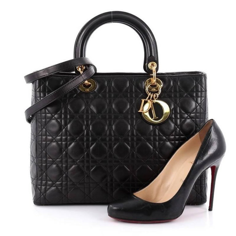This authentic Christian Dior Lady Dior Handbag Cannage Quilt Lambskin Large is a classic staple that every fashionista needs in her wardrobe. Crafted from black lambskin leather in Dior's iconic cannage quilting, this boxy bag features dual-rolled