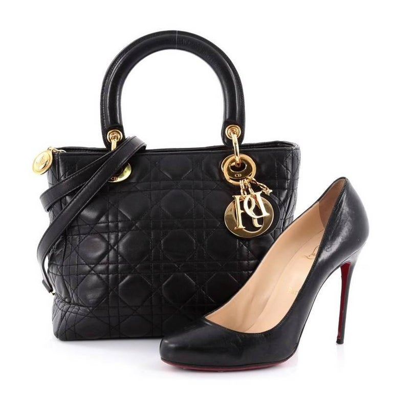 This authentic Christian Dior Lady Dior Handbag Cannage Quilt Lambskin Medium is an elegant classic bag that every fashionista needs in her wardrobe. Crafted from black lambskin leather in Dior's iconic cannage quilting, this boxy bag features short