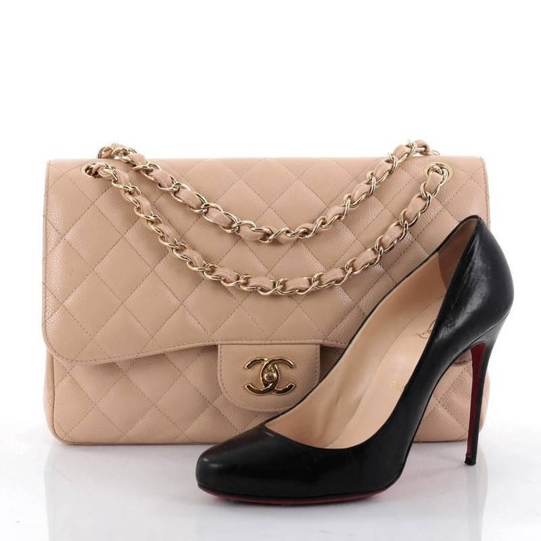 This authentic Chanel Classic Double Flap Bag Quilted Caviar Jumbo exudes a classic yet easy style made for the modern woman. Crafted from nude caviar leather, this elegant flap features Chanel's signature diamond quilted design, woven-in leather