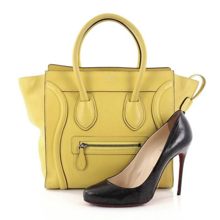 This authentic Celine Luggage Handbag Grainy Leather Micro is one of the most sought-after bags beloved by fashionistas. Crafted from yellow grainy leather, this minimalist tote features dual-rolled handles, an exterior front pocket, protective base