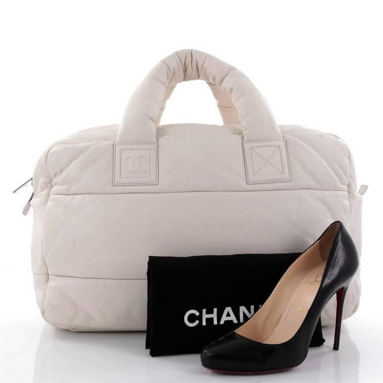 24e451e9d095 This authentic Chanel Coco Cocoon Bowling Bag Quilted Lambskin Large is a  highly sought after piece