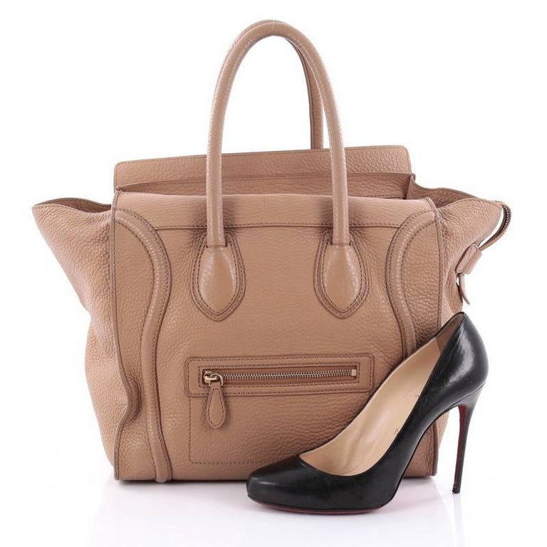This authentic Celine Luggage Handbag Grainy Leather Mini epitomizes Phoebe Philo's minimalist yet chic style. Constructed in light brown grainy leather, this beloved fashionista's bag features dual-rolled leather handles, a frontal zip pocket,