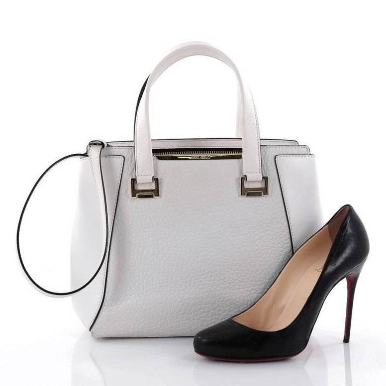 This authentic Jimmy Choo Alfie Handbag Leather Large is an understated, sleek tote made for all seasons. Crafted from white leather, this chic bag features dual-flat leather handles with metal top, protective base studs and gold-tone hardware