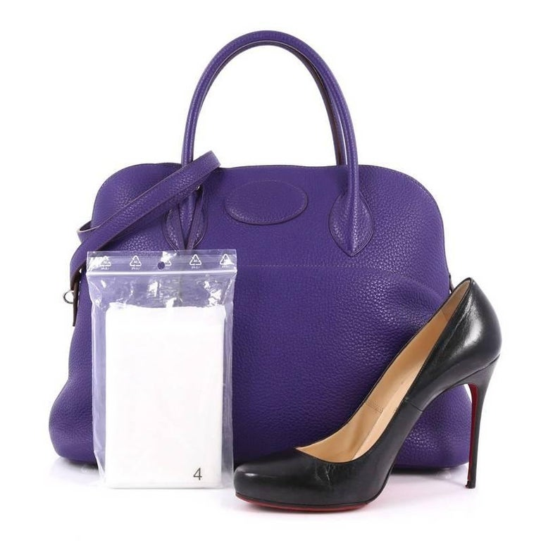 This authentic Hermes Bolide Handbag Clemence 35 is a classic, timeless piece essential for any Hermes lover. Dating back to 1923, the Bolide is the first Hermes bag to use a zipper design. Crafted from beautiful iris purple leather, this