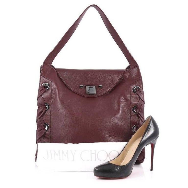 This authentic Jimmy Choo Rion Tote Leather is a stylish and fresh design perfect to add to your collection. Crafted in plum leather, this tote features dual flat looping leather handles, distinctive whipstitch detailing that adorns the edges of the