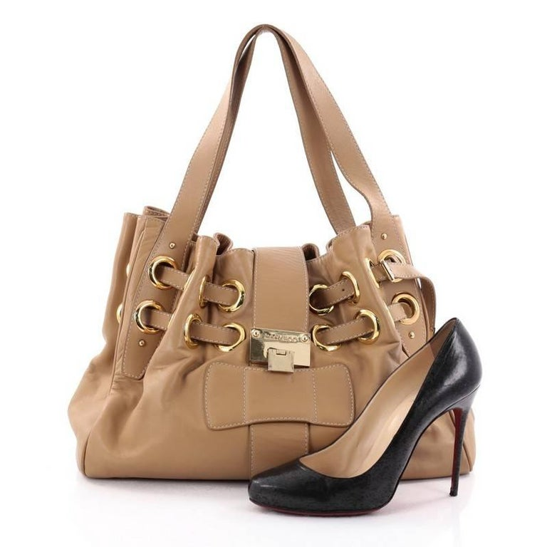 This authentic Jimmy Choo Ramona Hobo Leather is sophisticated and easy-to-carry made for everyday excursions. Constructed from supple beige leather, this hobo features multiple wrapped slim leather straps laced through metal eyelets, dual flat
