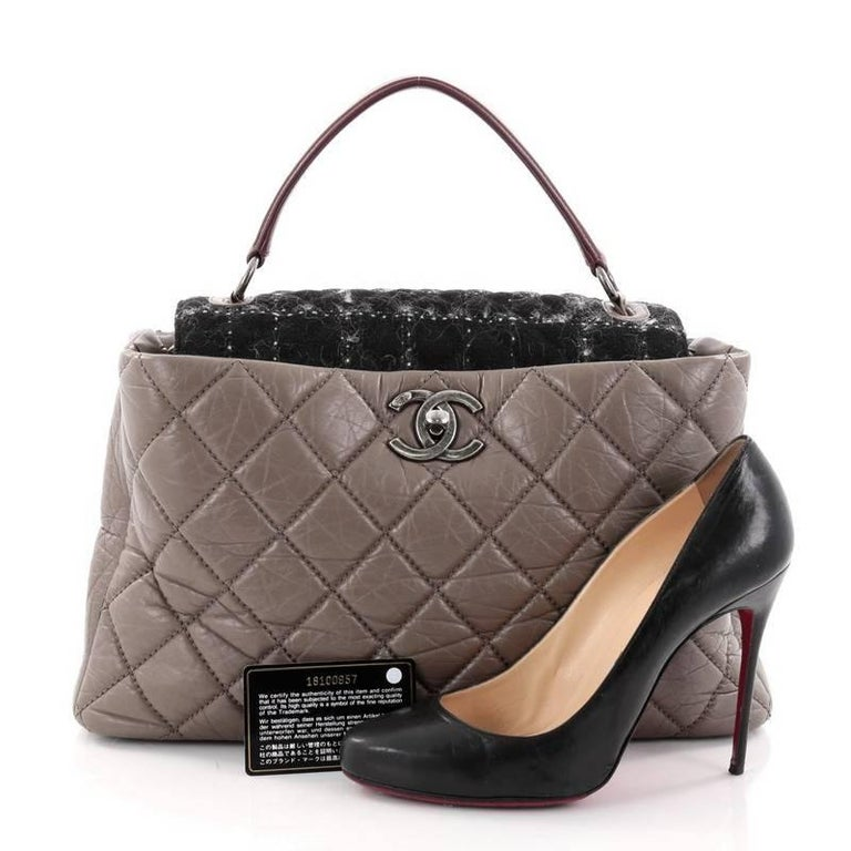 This authentic Chanel Portobello Top Handle Bag Quilted Aged Calfskin and Tweed Large is a gorgeous tote for day wear with a distinctive look. Crafted in taupe aged calfskin leather, this stylish tote features diamond quilted design, leather top