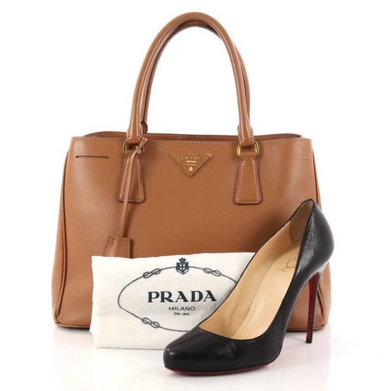 This authentic Prada Lux Open Tote Saffiano Leather Medium is elegant in  its simplicity and structure 0be8305672c31