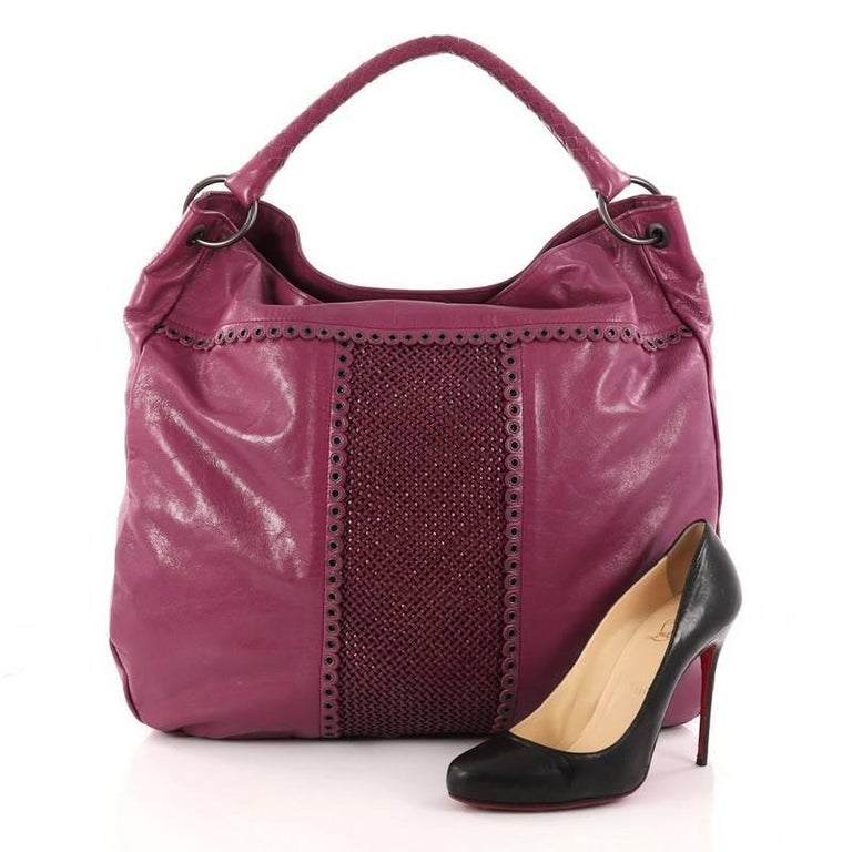 This authentic Bottega Veneta Hobo Leather with Grommet Detail Large is a timelessly elegant hobo made for everyday use. Crafted in purple leather with grommet detail, this no-fuss bucket hobo features a rolled looped strap and brunito- finished